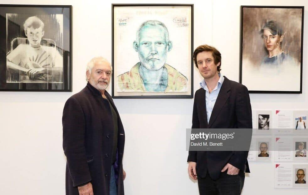 LONDON, ENGLAND - MARCH 14: Curator Ben Moore (R) with Artist Ricardo Cinalli (L) pose with his portrait from the Unmissable25 exhibition during the private view of The Other Art Fair at The Old Truman Brewery on March 14, 2019 in London, England. (Photo by David M. Benett/Dave Benett/Getty Images)
